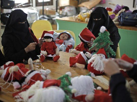 Palestinas vestidas con niqab fabrican muñecos de Papá Noel en Gaza
